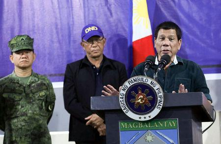 Philippine President Rodrigo Duterte speaks to soldiers next to Defence Secretary Delfin Lorenzana and Armed Forces chief General Eduardo Ano during a visit at a military camp in Iligan City, Philippines May 26, 2017.  Malacanang Presidential Palace/Handout via Reuters