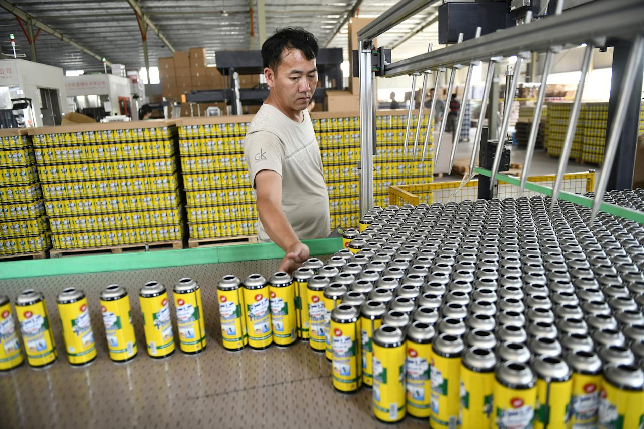 A man works on the production line manufacturing aerosol cans for export at a metal packaging manufacturer in Jinhua, Zhejiang province, China May 23, 2019. Picture taken May 23, 2019. REUTERS/Stringer ATTENTION EDITORS - THIS IMAGE WAS PROVIDED BY A THIRD PARTY. CHINA OUT.
