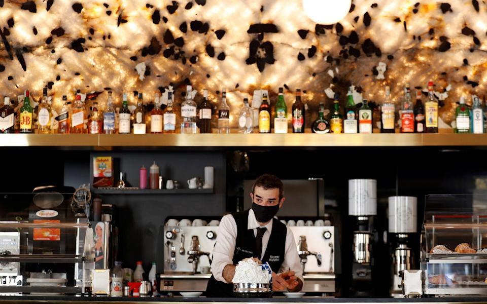 A waiter wearing a protective face mask works at a bar in Rome, Italy -  YARA NARDI / REUTERS