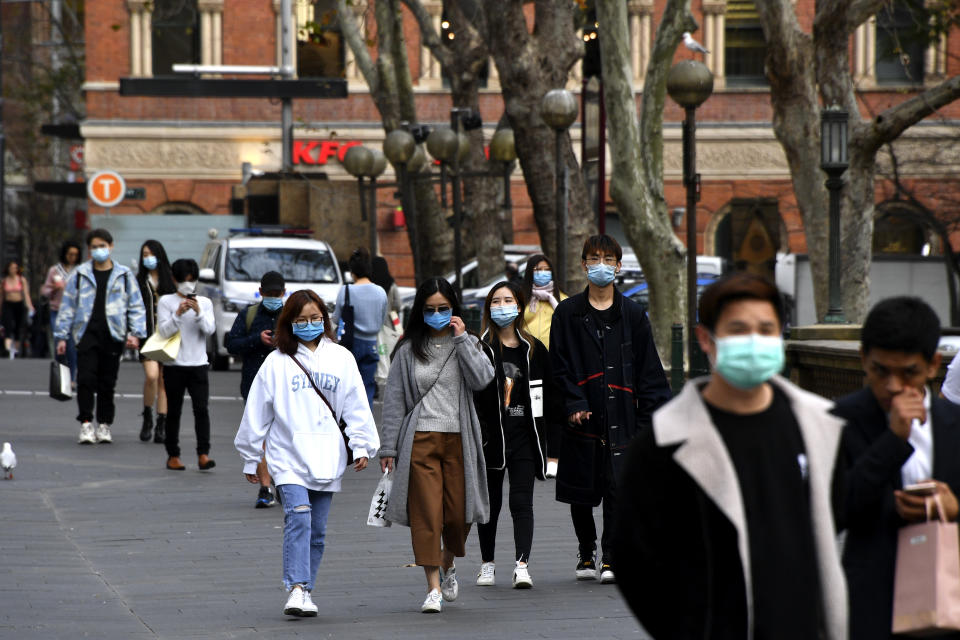 People wearing face masks walk on a street in the central business district of Sydney on August 3, 2020. - Australia's total reported infections of the COVID-19 coronavirus reached almost 18,000 in a population of 25 million. (Photo by Saeed KHAN / AFP) (Photo by SAEED KHAN/AFP via Getty Images)