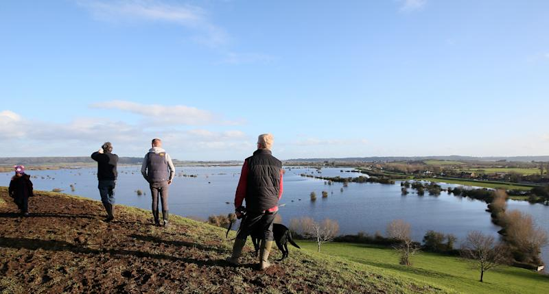 In this photo taken Sunday Feb. 2, 2014, people take photos and look at the flooding from the River Parrett on the Somerset Levels from Barrow Mump, Somerset, England, Here on the Somerset Levels _ a flat, marshy region of farmland dotted with villages and scored by rivers and ditches _ it's often wet. But not this wet. Thousands of acres of this corner of southwest England have been under water for weeks, some villages have been cut off for more than a month, and local people forced to take boats to get to school, work and shops are frustrated and angry. Some blame government budget cuts and environmental bureaucracy. Others point to climate change. Even plump, endangered water voles are the target of ire. (AP Photo/Alastair Grant)