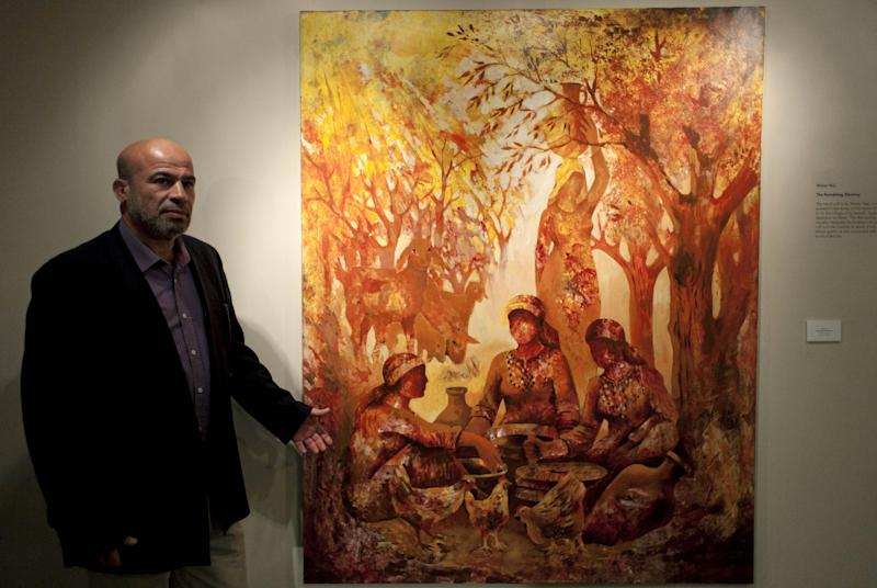 "In this photo taken Saturday, May 10, 2014, Palestinian artist Maher Naji poses next to his acrylic on canvas painting named The Remaining Memory, during an art exhibition ""Traces, a testimony to memory,"" displaying over forty Palestinian artists work from Gaza, in the West Bank city of Ramallah. The Gaza Strip is tough turf for artists. An Israeli-Egyptian border blockade of the Hamas-ruled territory keeps them away from an international audience and potential buyers, while the local art market is close to nil. A new exhibit now offers them a chance to showcase their work outside Gaza. (AP Photo/Nasser Nasser)"