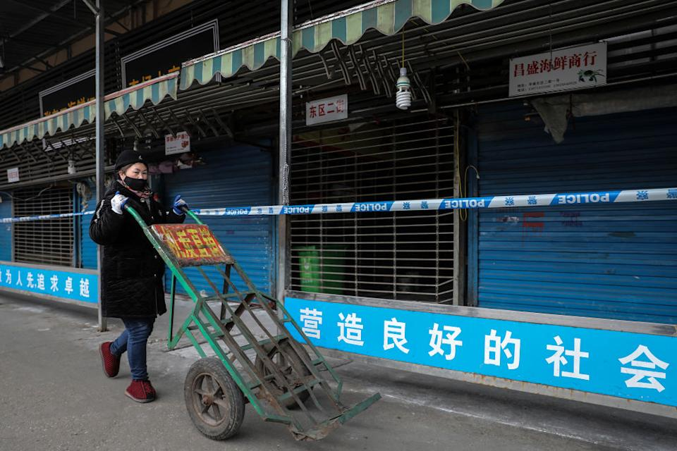 A woman walks past the closed Huanan Seafood Wholesale Market.
