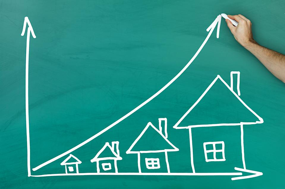 House prices growth concept on green blackboard