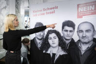 """Laura Zimmermann, Co-President of Operation Libero, is standing in front of a poster reading 'No. No Switzerland is an island."""" at the meeting place of the opponents of the popular initiative """"For moderate immigration"""" (the limitation initiative), on Sunday, 27 September 2020, at the Hotel Schweizerhof in Bern, Switzerland. (Peter Klaunzer/Keystone via AP)"""