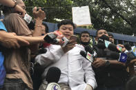 "Protest leader Parit ""Penguin"" Chiwarak reads from his mobile phone while speaking to journalists outside the criminal court after he was released on bail Saturday, Aug. 15, 2020 in Bangkok, Thailand. Parit was arrested by police Friday on a sedition charge in connection with a July 18 protest. (AP Photo/Busaba Sivasomboon)"