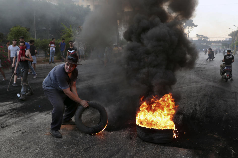 Protesters burn tires to block a road, in Beirut, Lebanon, Thursday, June 24, 2021. Dozens of angry protesters, angered by deteriorating living conditions and government inaction, partially blocked Beirut's main highway to the capital's only airport, turning trash bin over and setting tires on fire. (AP Photo/Bilal Hussein)