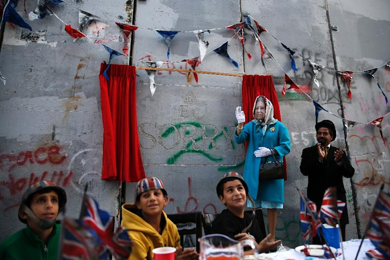 An actor dressed up as Britain's Queen Elizabeth hosts a party organised by secretive British street artist Banksy to apologise for the 1917 Balfour Declaration (AFP Photo/AHMAD GHARABLI)