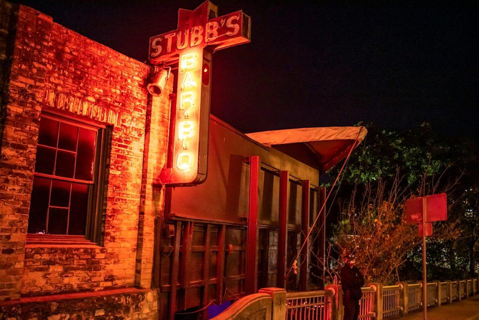A staff member stands outside Stubb's Bar-B-Q on Tuesday, Nov. 17, 2020, in Austin. Dave Chappelle announced a three night run in Austin. Attendees have to have a rapid COVID-19 test done before being able to enter.