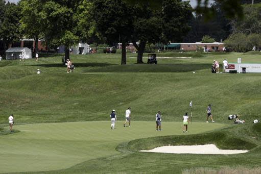 A group putts on the 17th green, below, during the first round of the LPGA Drive On Championship golf tournament at Inverness Golf Club in Toledo, Ohio, Friday, July 31, 2020. The tournament is being played with no fans due to COVID-19 safety protocol. (AP Photo/Gene J. Puskar)