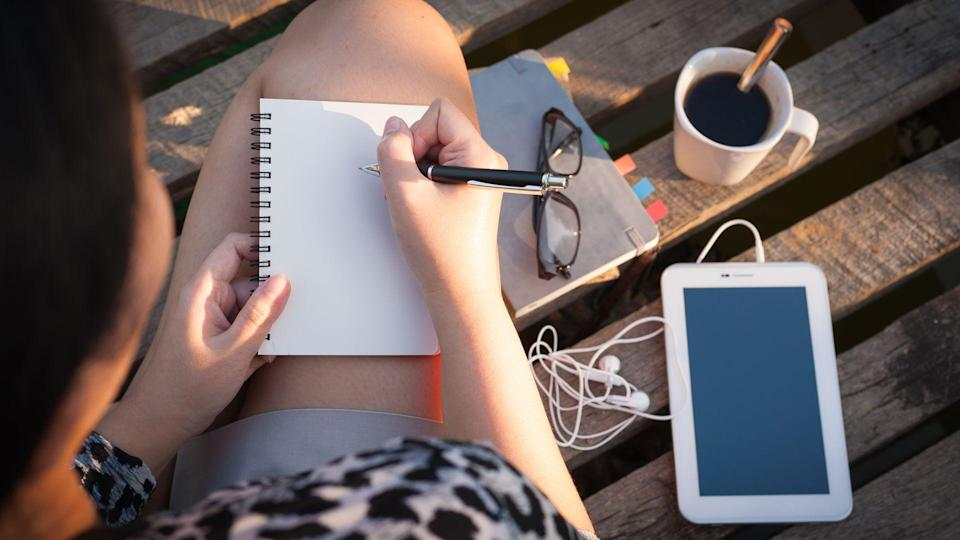 Young hipster woman writing journal on small notebook while sitting on wood bridge in morning time on weekend with high contrast sun lighting