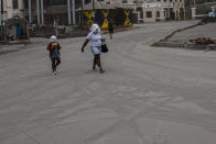 A woman and a girl walk wearing protective head coverings walk on a street covered with volcanic ash a day after the La Soufriere volcano erupted, in Kingstown, on the eastern Caribbean island of St. Vincent, Saturday, April 10, 2021. (AP Photo/Lucanus Ollivierre)