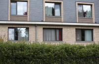 A resident in the window of a nursing home speaks with his relative from the window of his room at the Molenheide elderly care home in Wijnegem, Belgium on Tuesday, Aug. 18, 2020.Authorities in Belgium fear another deadly wave of coronavirus cases could soon hit care homes as the country confronts the risk of seeing its hospitals overwhelmed by COVID-19 patients, leading them to restrict nursing home visits. (AP Photo/Virginia Mayo)