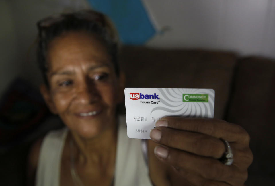 In this photo taken Wednesday, Aug. 14, 2019, Susie Garza displays the city provided debit card she receives monthly through a trial program in Stockton, Calif. Garza is participating in the Stockton Economic Empowerment Demonstration. The program, which started in February, gives $500 a month to 125 people who earn at or below the median household income of $46,033. They can spend the money with no restrictions. Stockton Mayor Michael Tubbs, who initiated the privately funded program, says it could be a solution to the city's poverty problem. (AP Photo/Rich Pedroncelli)