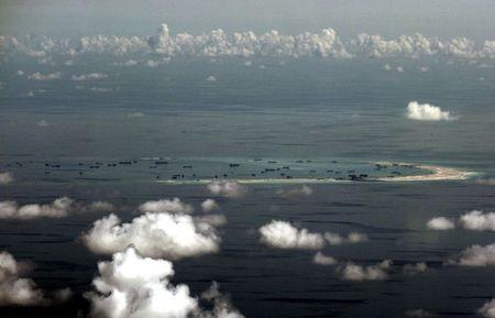 An aerial photo taken though a glass window of a Philippine military plane shows the alleged on-going land reclamation by China on mischief reef in the Spratly Islands in the South China Sea