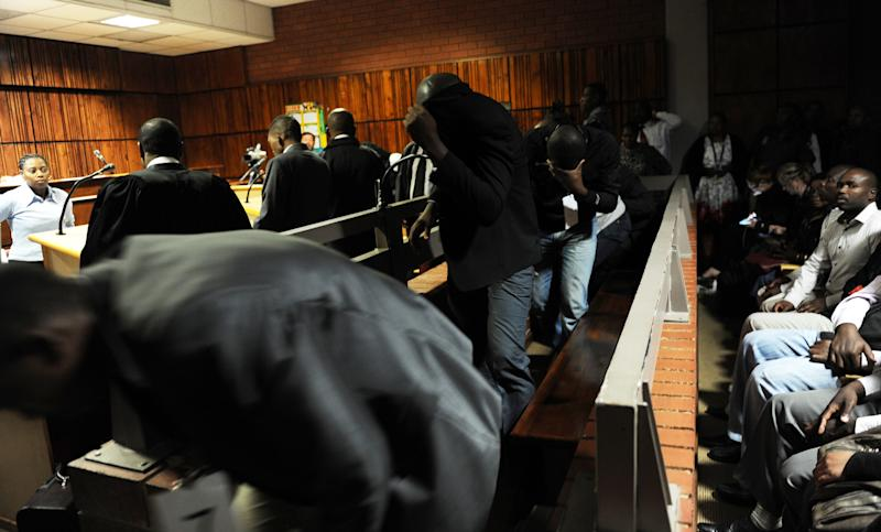 Policemen hide their faces as they appear in court for a bail hearing in Benoni, east of Johannesburg, Monday, March 11, 2013. Nine policemen are accused in the death of Mozambican taxi driver Mido Macia who was filmed being tied to the back of a police van and dragged along a street in Daveyton on February 26. He was found dead in the police station's holding cells several hours later. (AP Photo/Werner Beukes/Pool)