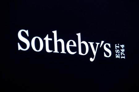 A screen shows the logo for Sotheby's on the floor at the NYSE in New York