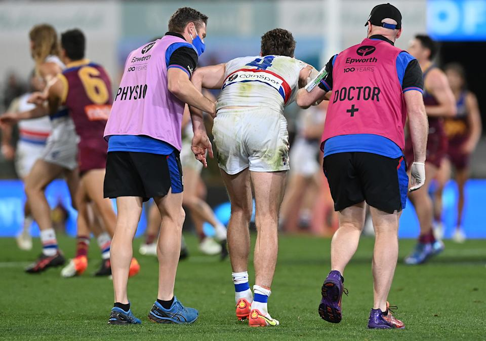 Seen here, Western Bulldogs captain Marcus Bontempelli comes off with a knee injury against the Lions.