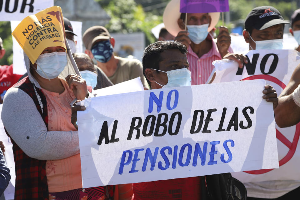 """A man holds a sign with a message that reads in Spanish; """"Don't steal our pensions,"""" during a protest against the country adopting Bitcoin as legal tender, along the Pan-American Highway, in San Vicente, El Salvador, Tuesday, Sept. 7, 2021. El Salvador became the first country to adopt Bitcoin as legal tender Tuesday, but the rollout stumbled in its first hours and President Nayib Bukele informed that the digital wallet used for transactions was not functioning. (AP Photo/Salvador Melendez)"""