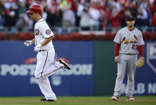 Washington Nationals' Adam LaRoche, left, rounds the bases past St. Louis Cardinals third baseman David Freese after hitting a solo home run in the second inning of Game 4 of the National League division baseball series on Thursday, Oct. 11, 2012, in Washington. (AP Photo/Alex Brandon)