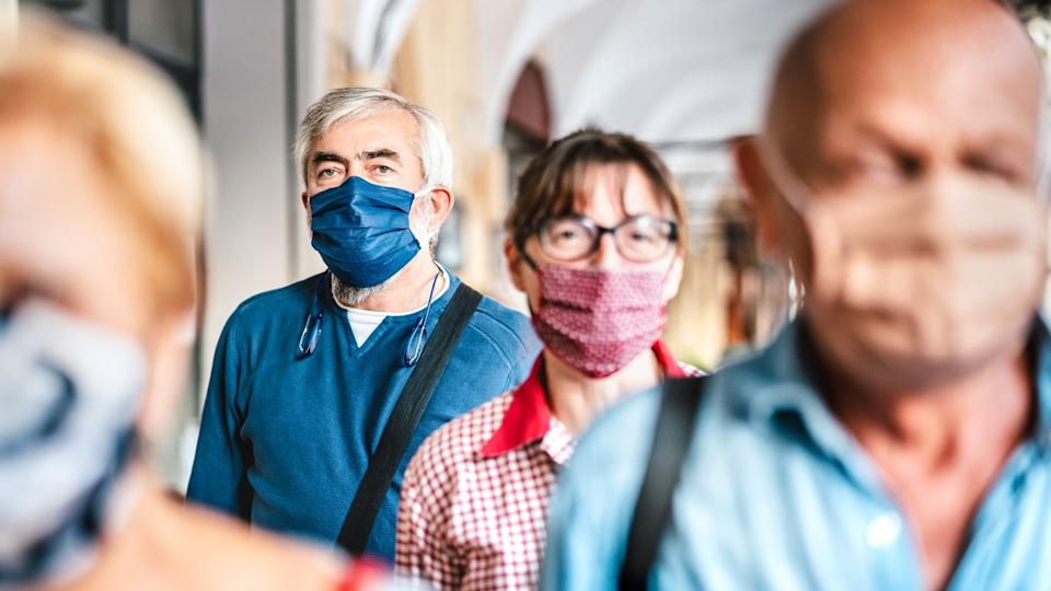 A crowd of people wearing face masks walk down a busy street in the city.