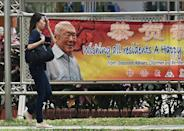 A pedestrian walks past a banner displaying an image of Singapore's founding leader Lee Kuan Yew in the port district of Tanjong Pagar, on March 17, 2015