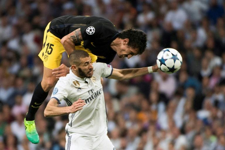 Atletico Madrid's defender Stefan Savic (L) jumps for the ball over Real Madrid's forward Karim Benzema on May 2, 2017