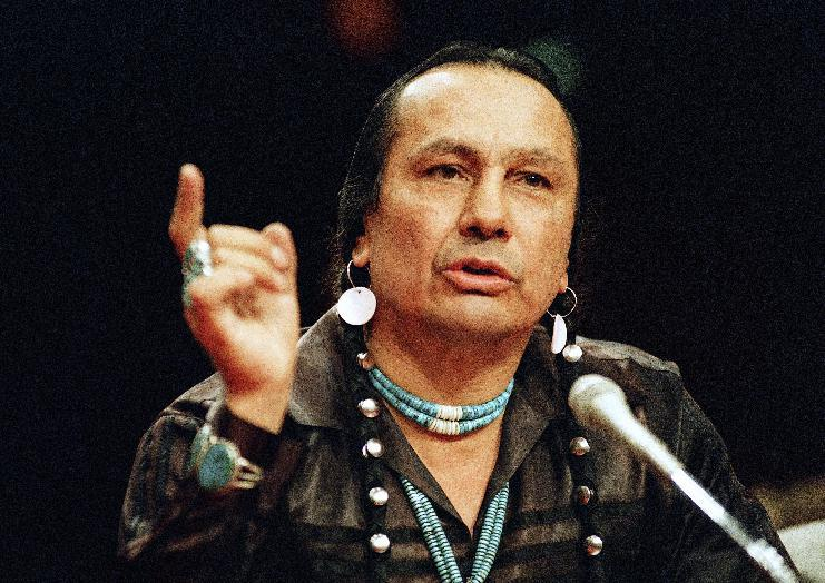 FILE - In a Jan. 31, 1989 file photo, Russell Means, who heads the American Indian Movement, (AIM) testifies before a special investigative committee of the Senate Select Committee on Capitol Hill, in Washington. Means, a former American Indian Movement activist who helped lead the 1973 uprising at Wounded Knee, reveled in stirring up attention and appeared in several Hollywood films, died early Monday, Oct. 22, 2012 at his ranch Zzxin Porcupine, S.D., Oglala Sioux Tribe spokeswoman Donna Solomon said. He was 72. (AP Photo/Marcy Nighswander, File)