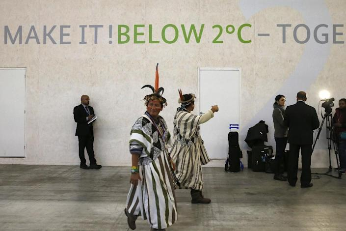 Lyndon Pishagua Chinchuga, a representative of the indigenous peoples of the Peruvian Amazon, walks past a stand at COP 21, the United Nations conference on climate change, at Le Bourget on December 3, 2015 More than 150 world leaders are meeting under heightened security, for the 21st Session of the Conference of the Parties to the United Nations Framework Convention on Climate Change COP21/CMP11) from November 30 to December 11. (AFP Photo/Patrick Kovarik)