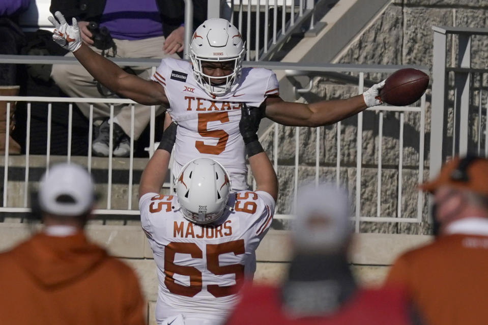 Texas running back Bijan Robinson (5) celebrates a touchdown with teammate Jake Majors (65).