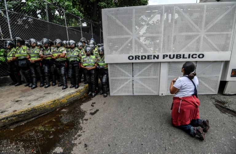 A woman kneels during a silent march by the opposition in a show of condemnation of the government of Venezuelan President Nicolas Maduro, in Caracas