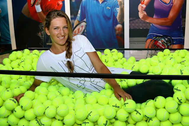 MELBOURNE, AUSTRALIA - JANUARY 17: Victoria Azarenka of Belarus poses in a box full of tennis balls during day two of the 2012 Australian Open at Melbourne Park on January 17, 2012 in Melbourne, Australia. (Photo by Robert Prezioso/Getty Images)