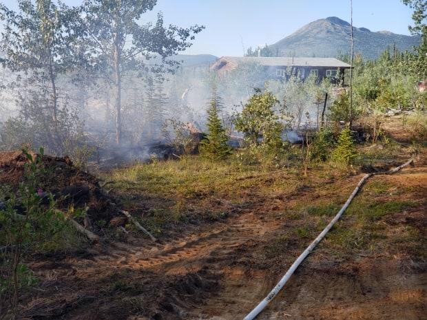 A small wildfire threatened a home in Haines Junction, Yukon on Friday evening but community members and fire crews were able to get it under control. (Submitted by Wally Bootsma - image credit)