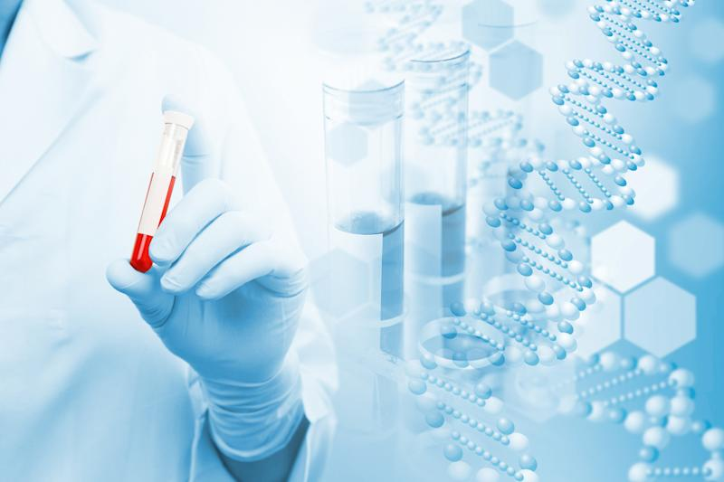 Person in a white coat holding a vial of blood with images of test tubes and DNA in the background