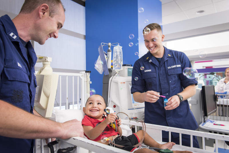 Coast Guard Lt. Brad Bryan (left) and Ensign James Gardner play with Zaiden Thomas, a dialysis patient who the two Guardsmen helped rescue during the floods caused by Hurricane Harvey. On Labor Day, the pair met some of the patients they delivered to Texas Children's Hospital in Houston and the staff with whom they coordinated the missions. (Allen S Kramer/Texas Childrens Hospital)