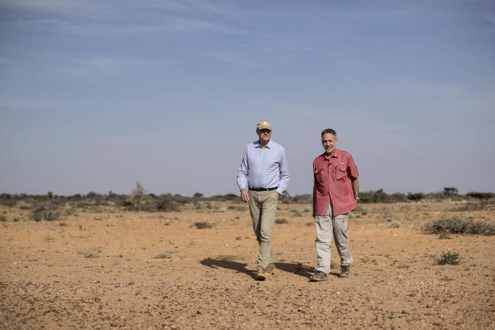 In this photo taken Wednesday, Feb. 5, 2020, Dominique Burgeon, center, Director of the Emergency and Resilience Division of the Food and Agriculture Organization (FAO) and Keith Cressman, right, Senior Locust Forecasting Officer for FAO, walk in the desert between Garowe and Qardho, in the semi-autonomous Puntland region of Somalia. The desert locusts in this arid patch of northern Somalia look less ominous than the billion-member swarms infesting East Africa, but the hopping young locusts are the next wave in the outbreak that threatens more than 10 million people across the region with a severe hunger crisis. (AP Photo/Ben Curtis)