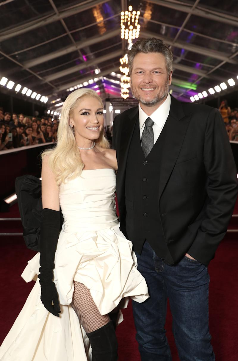 Gwen Stefani (left) wears a white ruffled mullet dress and Blake Shelton (right) wears a suit jacket and jeans. Both pose for the camera