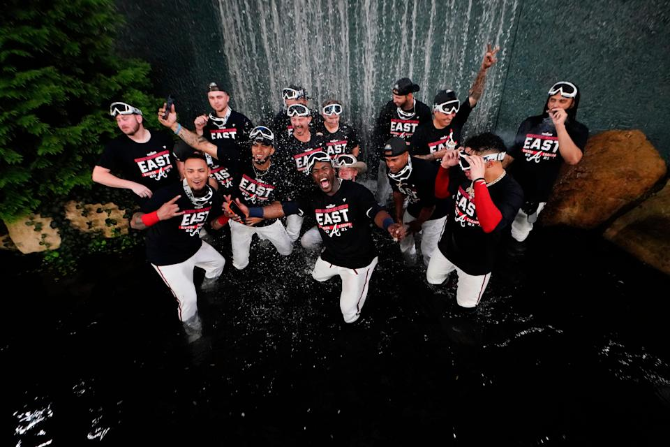 The Atlanta Braves players celebrate in a fountain after a baseball game against the Philadelphia Phillies, Thursday, Sept. 30, 2021, in Atlanta. The Atlanta Braves clinched the NL East title against the Philadelphia Phillies. (AP Photo/John Bazemore)