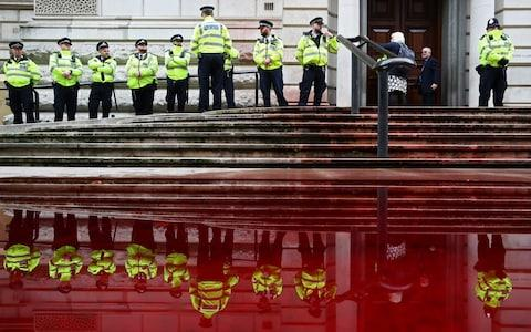 <span>Police stand in front of the Treasury building</span> <span>Credit: SIMON DAWSON/REUTERS </span>