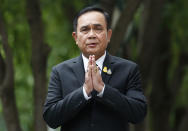 """Thailand's Prime Minister Prayuth Chan-ocha gives the traditional greeting, or """"wai,"""" as he talks to reporters before meeting at government house in Bangkok, Thailand, Thursday, June 6, 2019. Thailand's Parliament elected 2014 coup leader Prayuth Chan-ocha as prime minister in a vote Wednesday that helps ensure the military's sustained dominance of politics since the country became a constitutional monarchy nearly nine decades ago. (AP Photo/Sakchai Lalit)"""