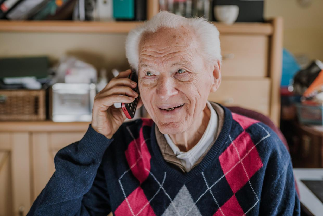 Old man using phone sitting at desk. Order food home with delivery, shopping ordered by phone. Phone call from family. Medical consultations by phone. Quarantine during virus Covid-19 pandemic.