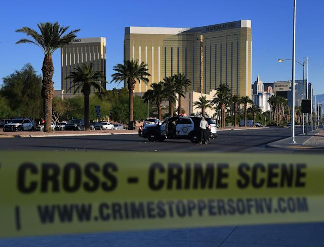 <p>Crime scene tape surrounds the Mandalay Hotel (background) after a gunman killed at least 50 people and wounded more than 200 others when he opened fire on a country music concert in Las Vegas, Nevada on Oct. 2, 2017. (Photo: Mark Ralston/AFP/Getty Images) </p>