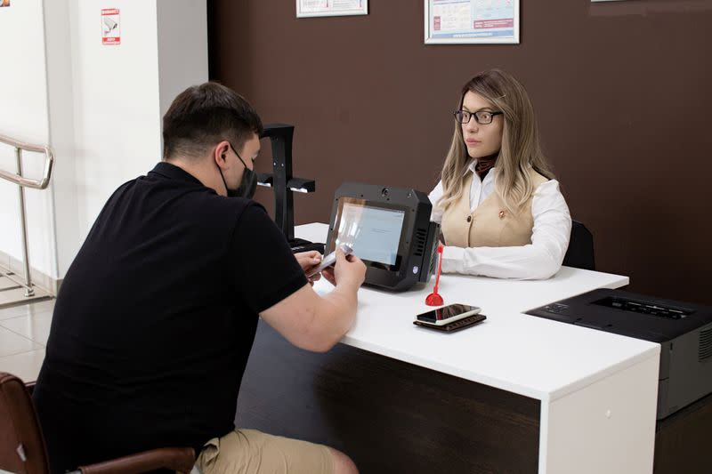 A female human-like robot assists a visitor at a document processing centre in Perm