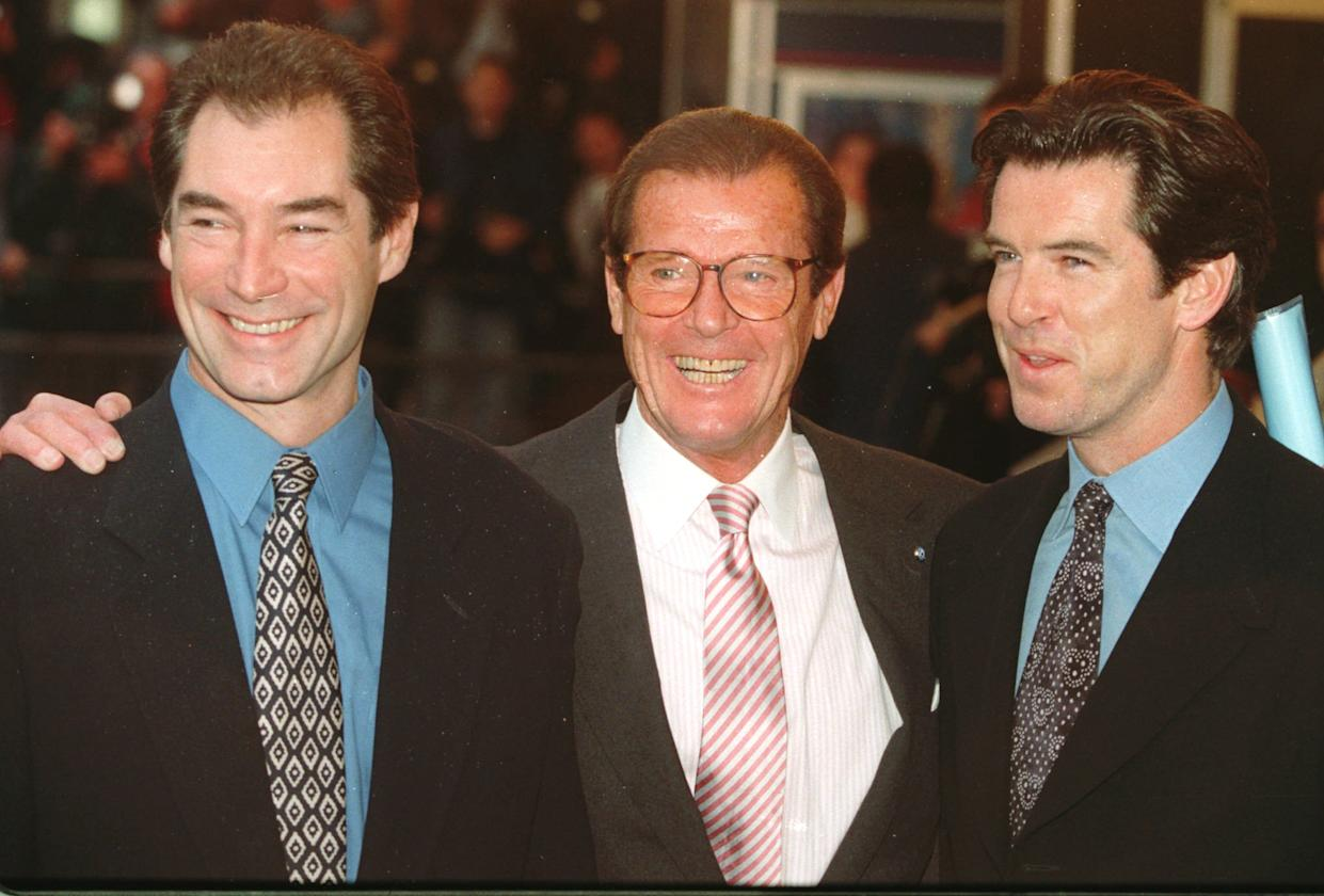 """Timothy Dalton left, Roger Moore and Pierce Brosnan, three of the actors who have portrayed the English secret agent James Bond in the Bond movies line up at a central London cinema to celebrate the life of Albert R. """"Cubby"""" Broccoli Sunday, Nov. 17, 1996. The American film producer Broccoli was responsible for the seventeen Bond movies from 'Dr. No' to the recent 'Goldeneye'.(AP Photo/Alastair Grant)"""