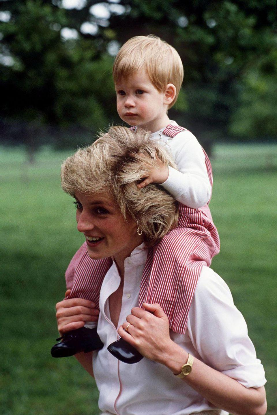 <p>Harry places his hands on Princess Diana as she holds him on her shoulders at Highgrove House.</p>