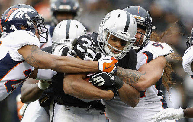 <p>Oakland Raiders running back DeAndre Washington (33) is tackled by Denver Broncos defenders during the first half of an NFL football game in Oakland, Calif., Sunday, Nov. 26, 2017. (AP Photo/D. Ross Cameron) </p>