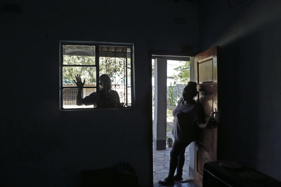 Andrew Ngwenya, left, and his wife, De-egma, are seen at their home in a working class township in Harare, the capital Zimbabwe, on Monday, July, 12, 2021. Ngwenya and his wife went to a hospital that sometimes had spare doses of the COVID-19 vaccine, only to be turned away due to shortages. (AP Photo/Tsvangirayi Mukwazhi)