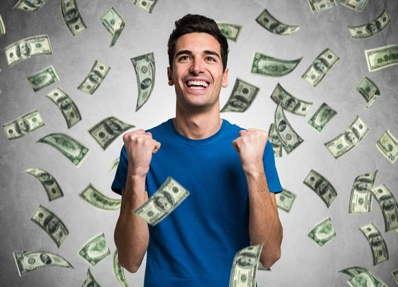 Smiling man with money raining down on him