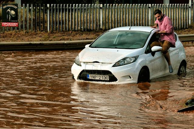 <p>A man tries to get into a car stuck in floodwater in the town of Mandra, northwest of Athens, on Nov. 15, 2017. (Photo: Valerie Gache/AFP/Getty Images) </p>