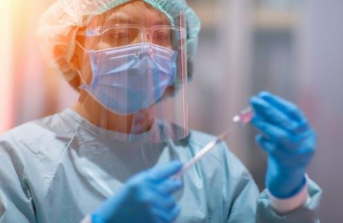 """<span class=""""caption"""">Counterfeit vaccines, testing kits, and vaccine passports are undermining the global fight against COVID-19.</span> <span class=""""attribution""""><a class=""""link rapid-noclick-resp"""" href=""""https://www.shutterstock.com/image-photo/doctor-lab-technician-scientist-ppe-personal-1741477487"""" rel=""""nofollow noopener"""" target=""""_blank"""" data-ylk=""""slk:AnaLysiSStudiO/Shutterstock"""">AnaLysiSStudiO/Shutterstock</a></span>"""